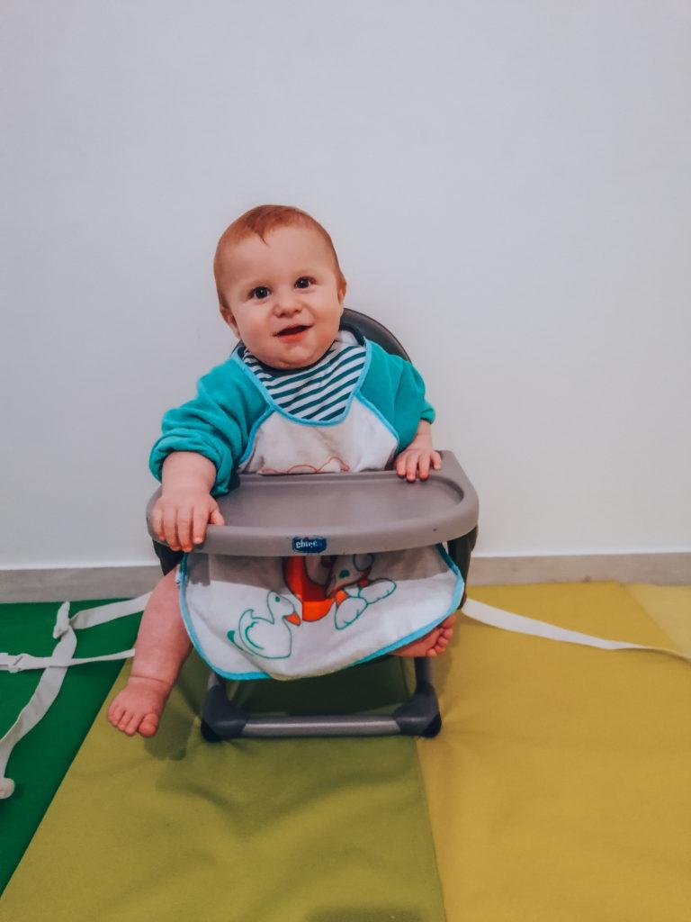 Bébé sur son réhausseur de chaise pour la DME