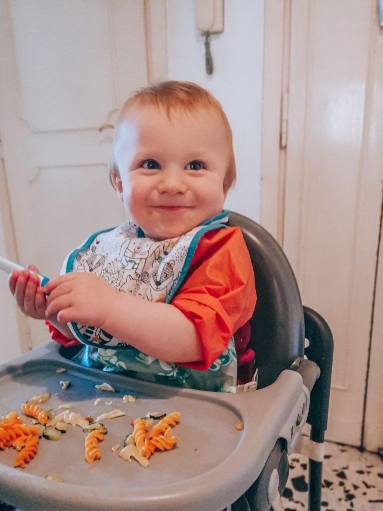 Motricité fine de bébé de 1 an qui tient une cuillère à table