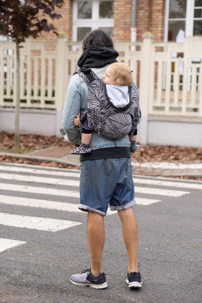 Bébé porté par son papa dans le porte bébé onbuhimo SAD de Fidella