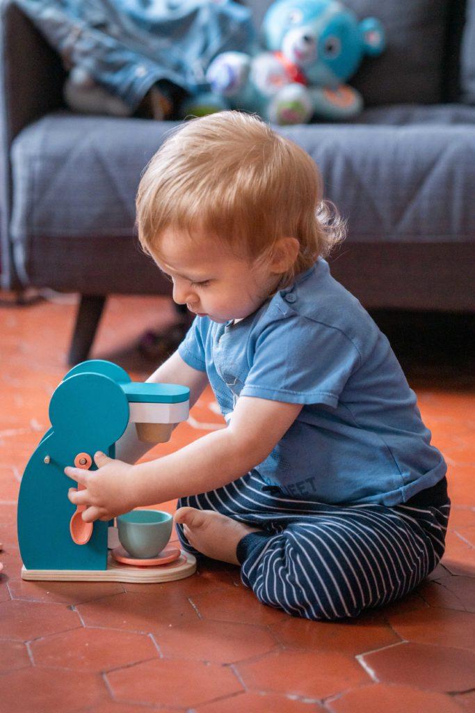 Bébé en train de faire un café avec une cafetière jouet Amis Monstres